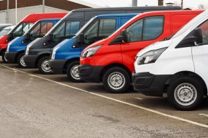 row of different marques of commercial vehicles or vans for retail sale on a motor dealers lot all logos removed