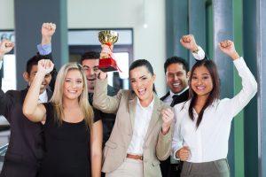 cheerful business team winning an award for their performance